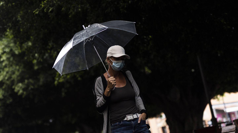 Por la calle, con paraguas para evitar la ceniza. (Alejandro Martínez)
