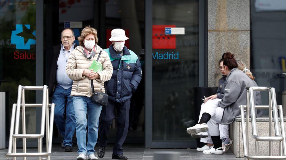 Foto: Dos personas mayores con mascarilla caminan junto a la entrada de un hospital. (EFE)