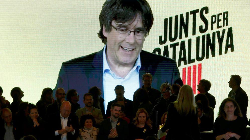 Foto: El expresidente catalán Carles Puigdemont (en la pantalla, por videoconferencia desde Bruselas) interviene en un acto de de campaña de JxCAT en Barcelona. (EFE)