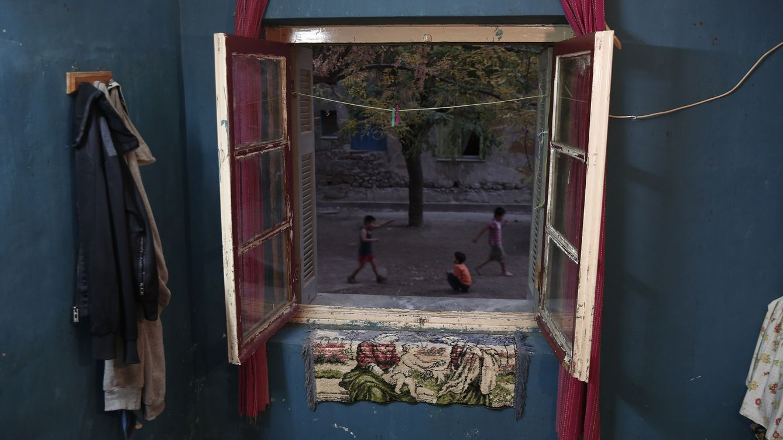 """Foto: Unos niños que juegan en la calle vistos desde un apartamento en el complejo de viviendas """"Profygika"""", en Atenas, en noviembre de 2013. (Reuters)"""