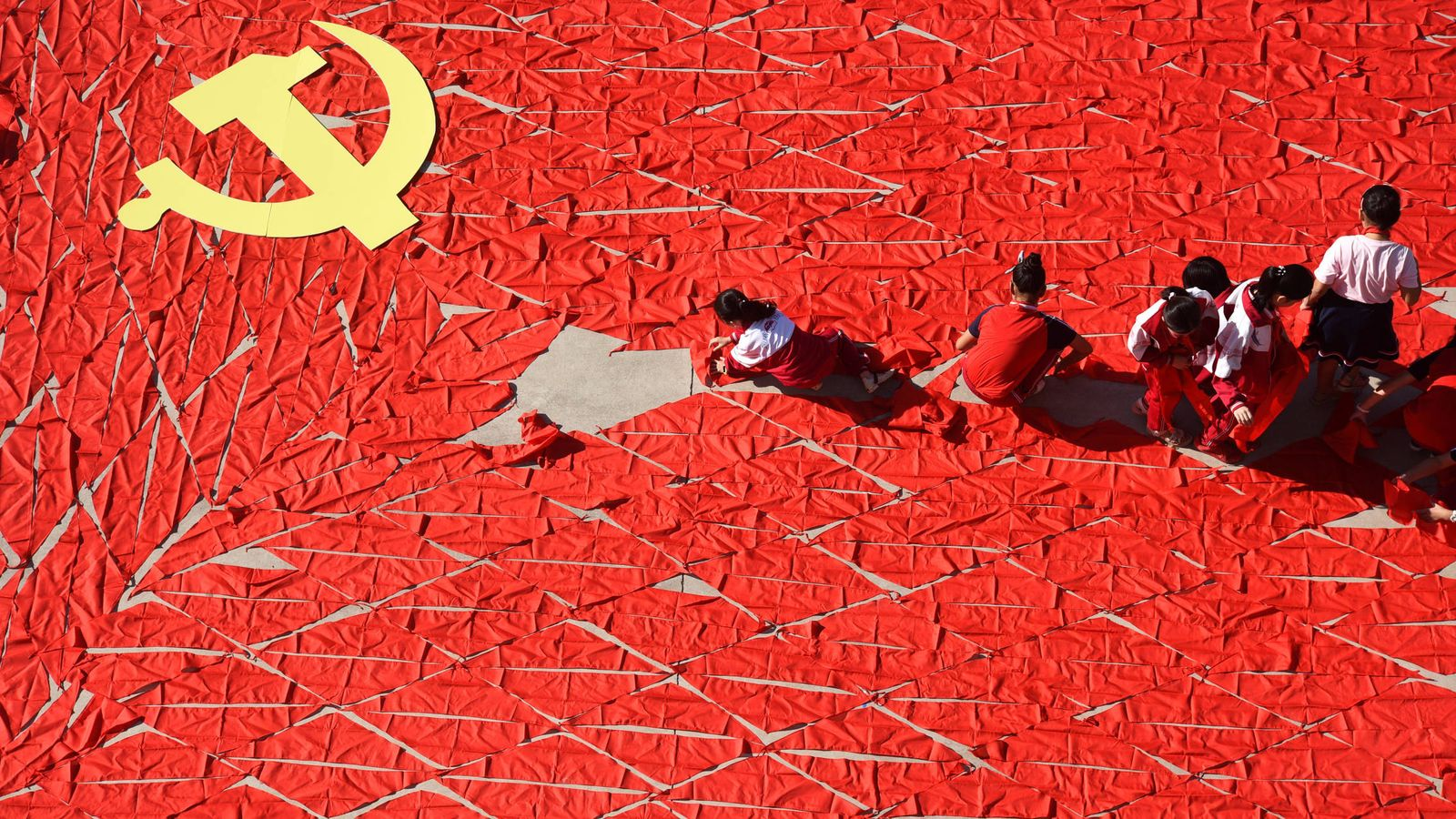 Foto: Estudiantes chinos utilizan alfombras rojas para formar una bandera antes del Congreso Nacional del PCCh, en Linyi, provincia de Shandong. (Reuters)