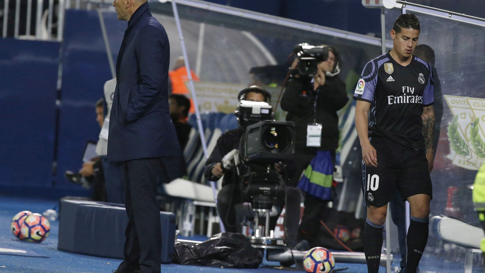 Foto: James, cabizbajo, pasa por detrás de Zidane en un partido del Real Madrid. (EFE)