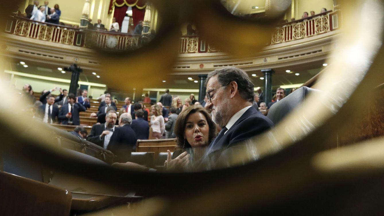 Foto: Mariano Rajoy (d), conversa con la vicepresidenta, Soraya Sáenz de Santamaría, antes del inicio del pasado debate de investidura del líder del PP. (EFE)