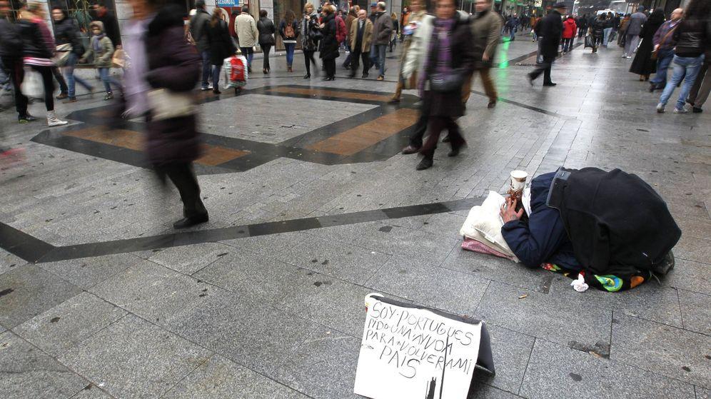 Foto: Un indigente pide ayuda en la madrileña calle de Preciados. (EFE)