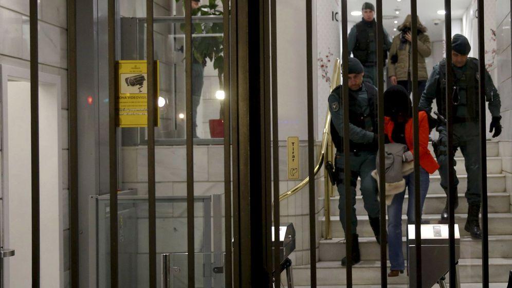 Foto: Agentes de la Guardia Civil trasladan a varios detenidos en la intervención del banco chino ICBC. (EFE)