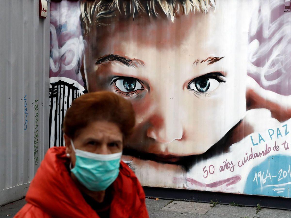 Foto: Una mujer con mascarilla pasa junto a un mural en el Hospital La Paz de Madrid. (EFE)