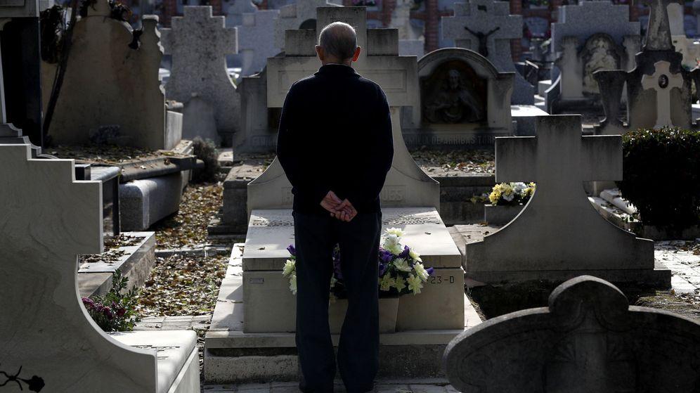 Foto: Un hombre frente a una sepultura en el cementerio de La Almudena de Madrid. (EFE)