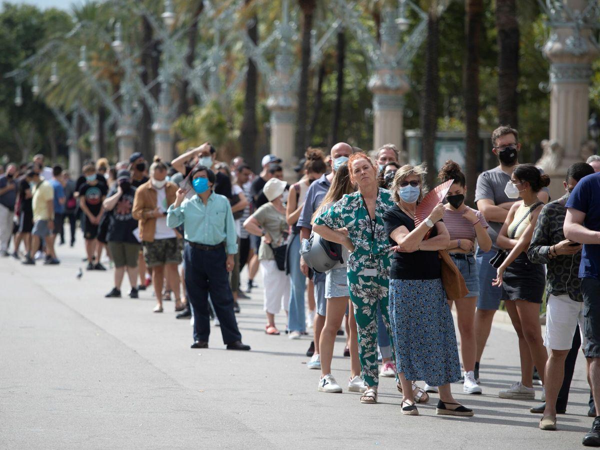 Foto: Numerosas personas esperan para vacunarse en un punto móvil instalado en Arco de Triunfo, en Barcelona. (EFE)