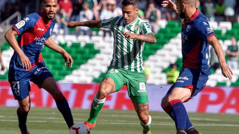 Foto: El delantero del Real Betis, Cristian Tello (c), disputa el balón ante el Huesca durante el partido de Liga perteneciente a la jornada 37. (EFE)