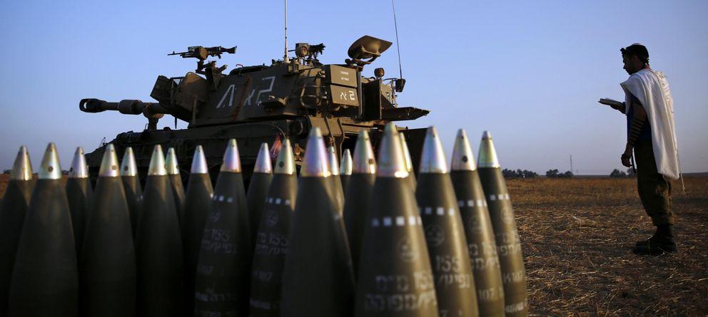 Foto: Un soldado del Ejército israelí reza junto a una pieza de artillería cerca de la frontera de Gaza (Reuters).
