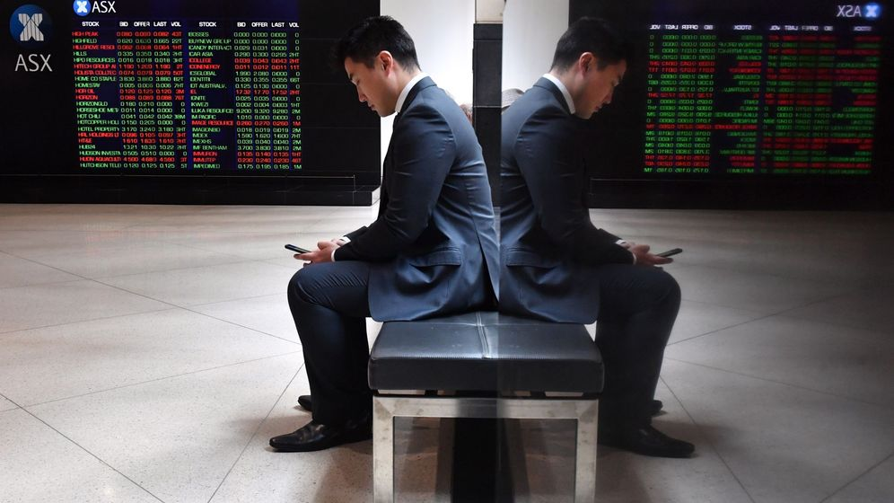 Foto: Un hombre revisa su teléfono junto a los indicadores de la Bolsa australiana (ASX). (EFE)