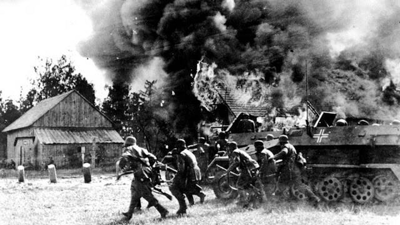 Soldados alemanes atraviesan una aldea rusa incendiada en junio de 1941