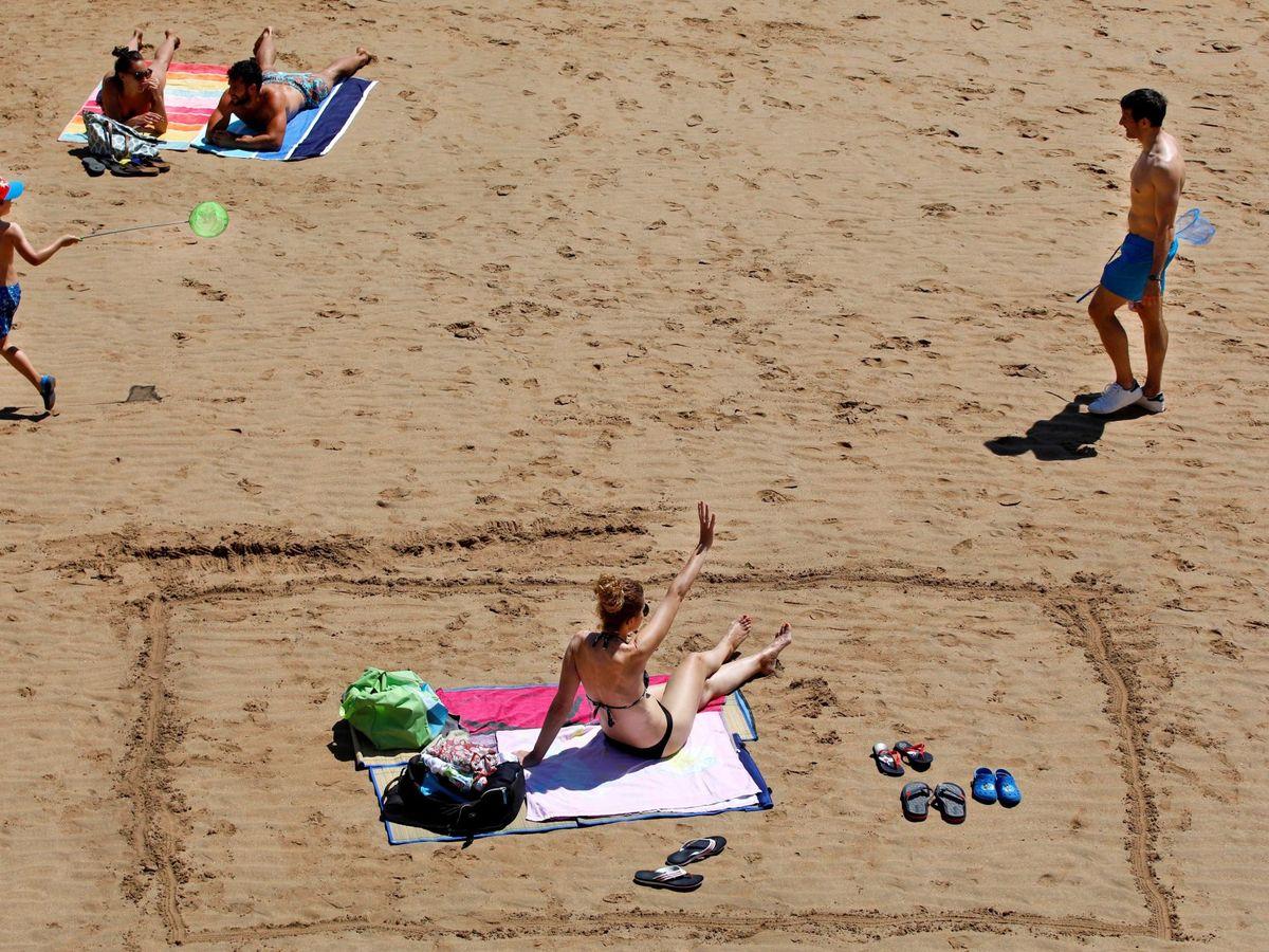 Foto: Varias personas disfrutan de un soleado día de verano en la playa de San Lorenzo en Gijón. (EFE)
