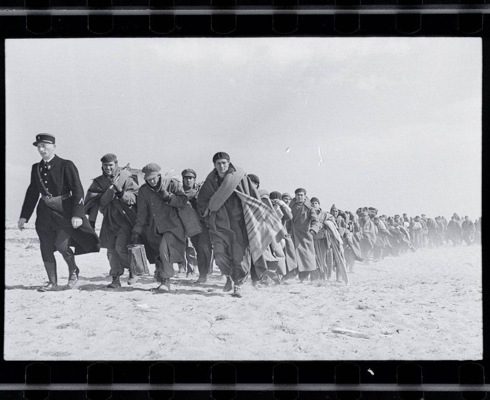 Foto: Uno de los negativos del libro 'La maleta mexicana', de Robert Capa, que muestra a unos exiliados republicanos caminando por una playa francesa, en 1939.  (EFE/Robert Capa)