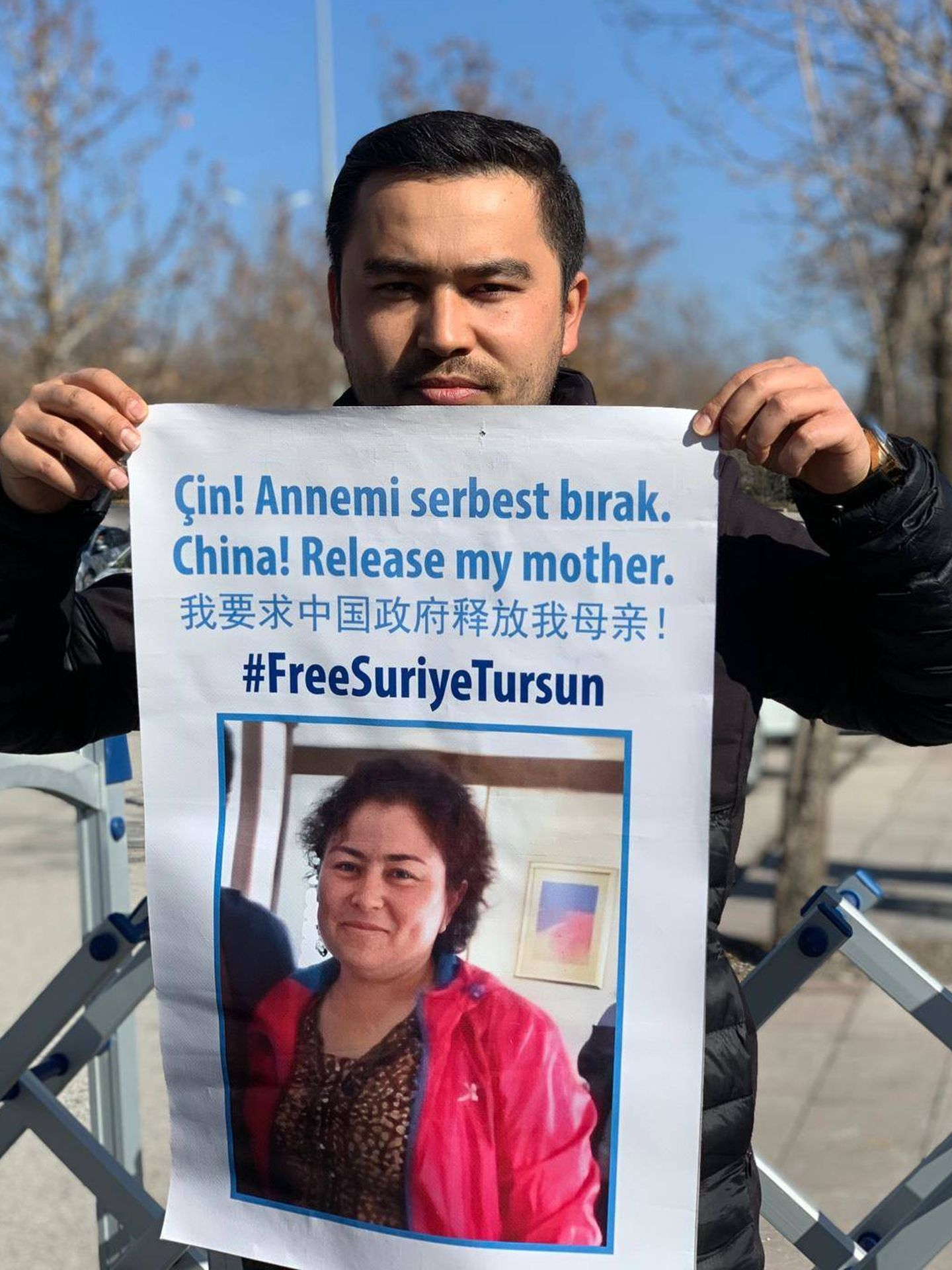 Jevlan Shirmemmet sostiene un cartel en el que pide por la liberación de su madre en una protesta en Turquía