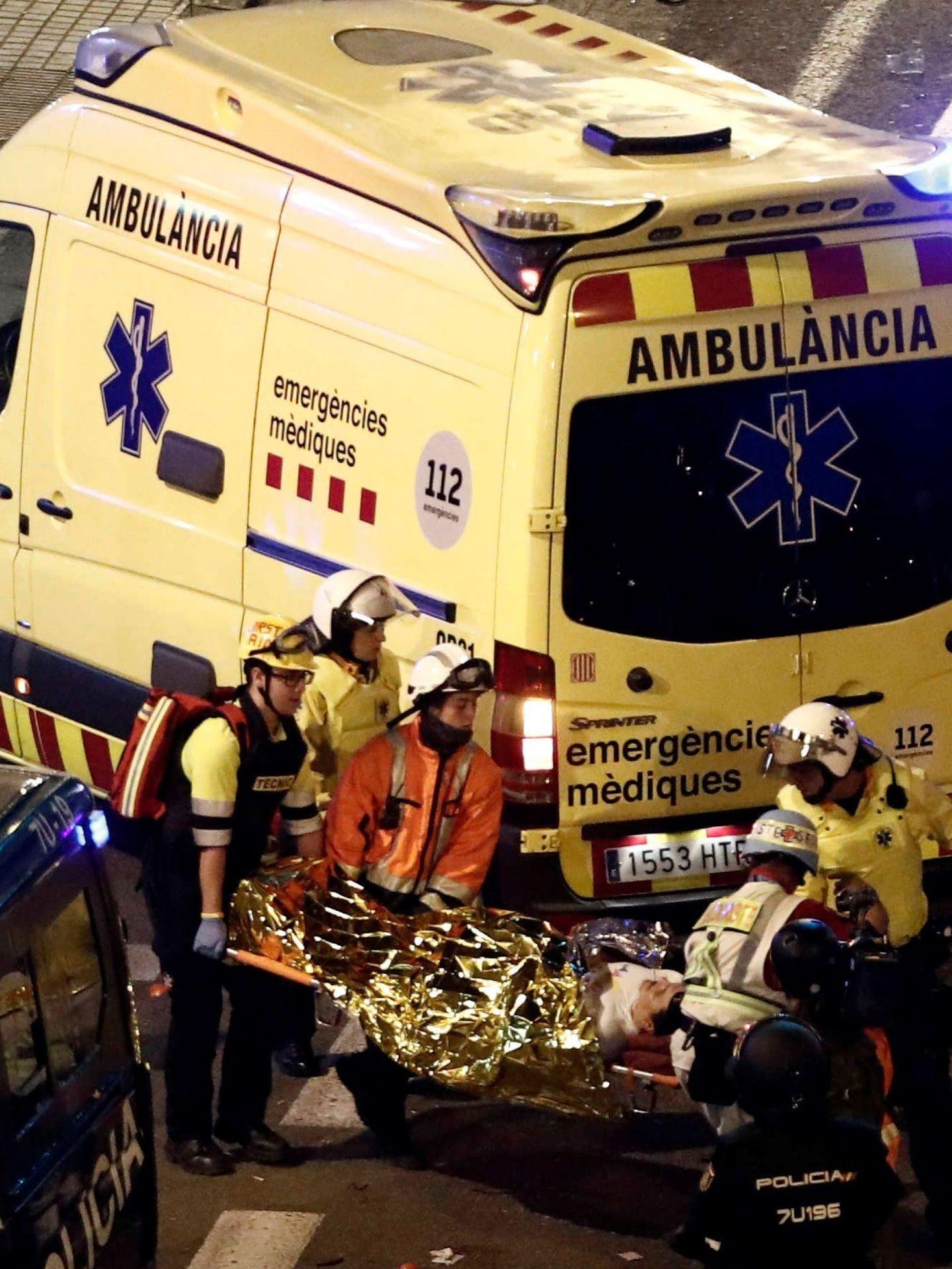 Varios sanitarios transportan a un herido en los enfentamientos de Vía Laietana. (EFE)