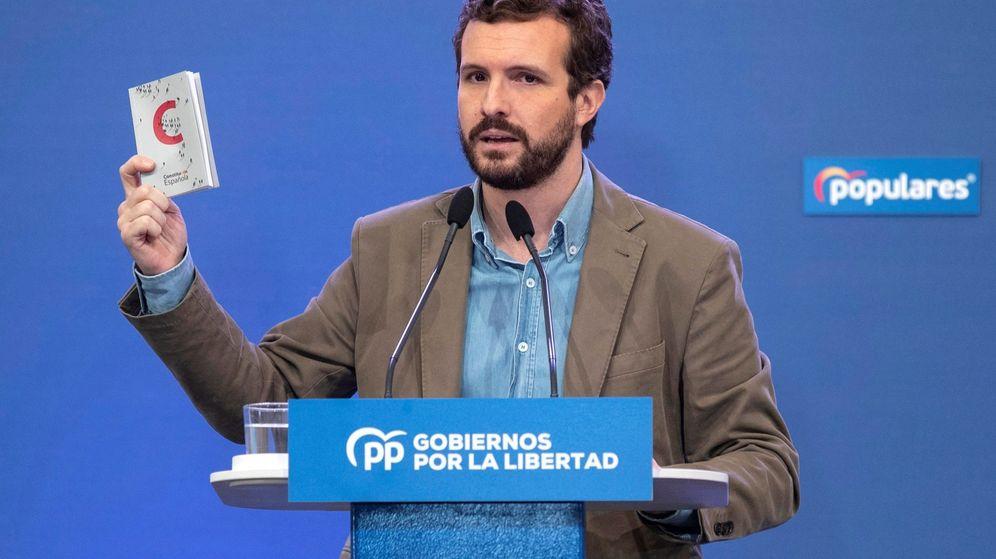 Foto: El presidente del PP, Pablo Casado, muestra un ejemplar de la Constitución durante su intervención en un acto del partido. (EFE)
