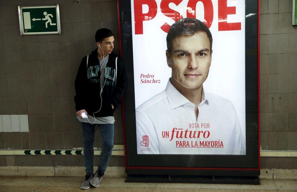 Foto: Un hombre junto un cartel electoral de Pedro Sánchez este 21 de diciembre, en Madrid. (Reuters)