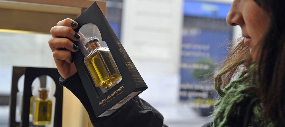 Foto: Una turista observa una botella de aceite de los olivares centenarios de la Alhambra. (Efe)