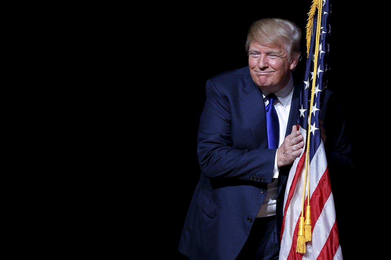 Foto: El candidato presidencial republicano Donald Trump abraza una bandera de EEUU durante un mitin electoral en Derry, New Hampshire, el 19 de agosto de 2015 (Reuters).