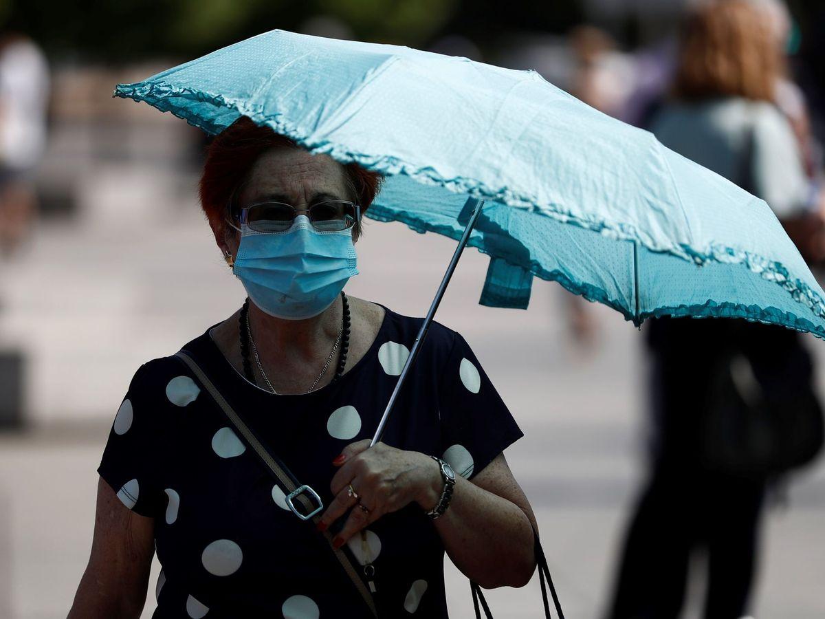Foto: Una mujer pasea por Madrid protegida con una sombrilla (EFE)