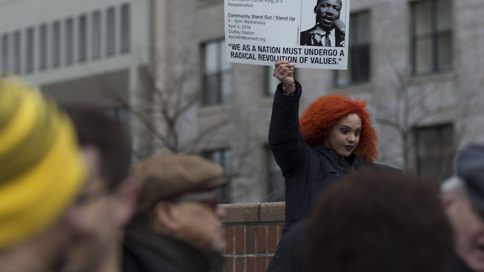 Foto: Una joven sostiene un cartel durante la lectura del discurso final de Martin Luther King en Boston, durante el aniversario de su muerte, el 2 de abril de 2018. (EFE)