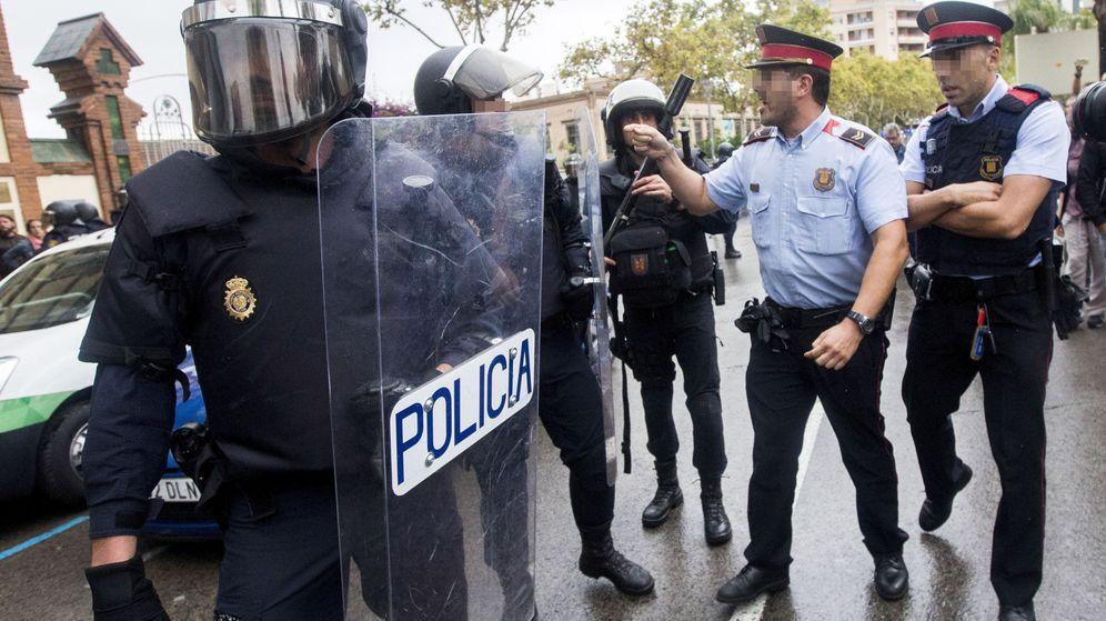 Foto: Agentes de la Policía Nacional y de los Mossos d'Esquadra discuten ante un colegio electoral. (EFE)