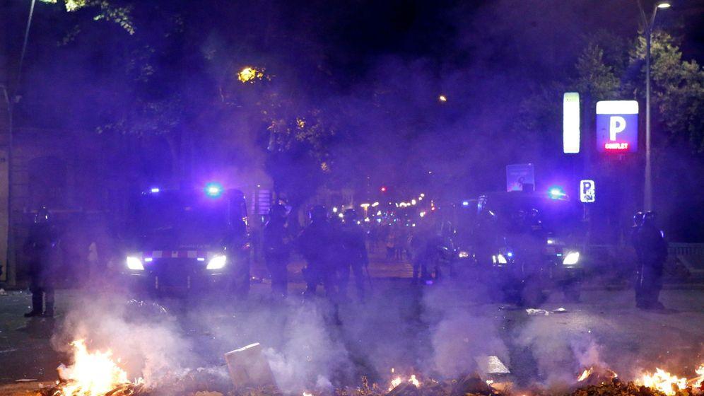 Foto: Mossos d'esquadra ante una barricada de fuego en Paseo de Gracia. (EFE)