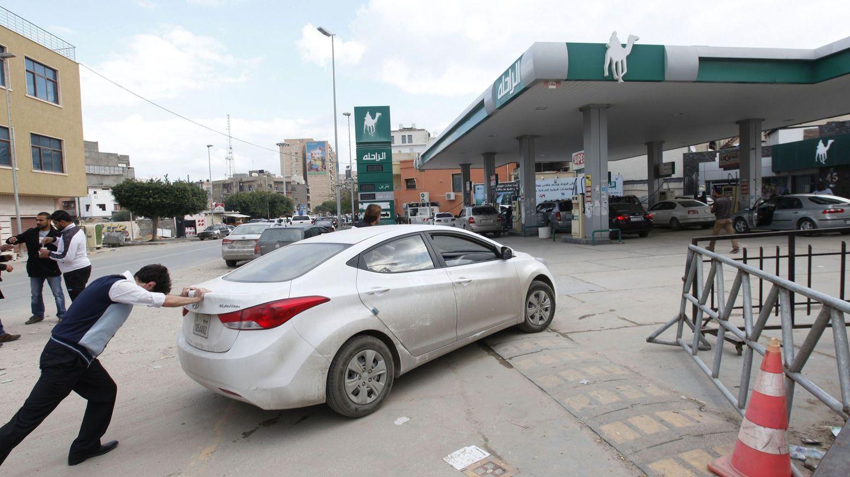 Un hombre empuja su coche hasta una estación de servicio tras quedarse sin gasolina en Trípoli (Reuters).