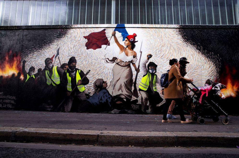 Foto: Personas pasan frente a un mural del artista francés Pascal Boyart sobre los chalecos amarillos que versiona la obra de Eugene Delecroix La libertad guiando al pueblo. (EFE)
