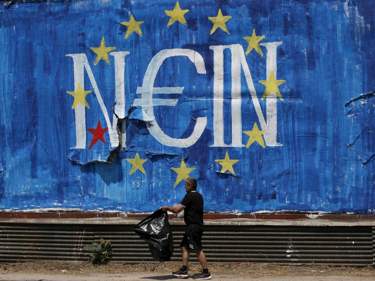 Foto: Un hombre pasea ante un graffiti contra el euro en Grecia. (Reuters)