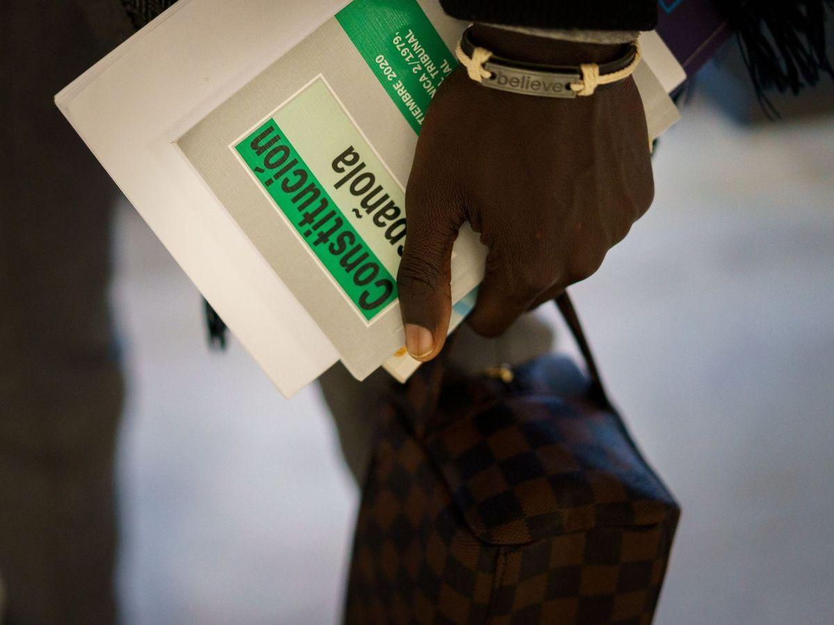 Foto: Un inmigrante senegalés porta una edición de la Constitución española. (EFE)
