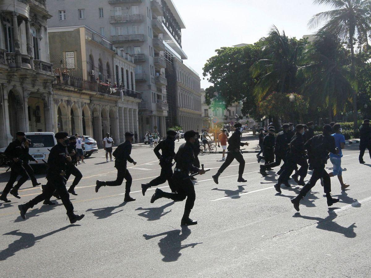 Foto: Agentes de policía corren durante manifestaciones en La Habana. (Reuters)