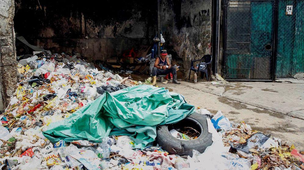 Foto: Un hombre descansa junto a basura en Caracas. (EFE)