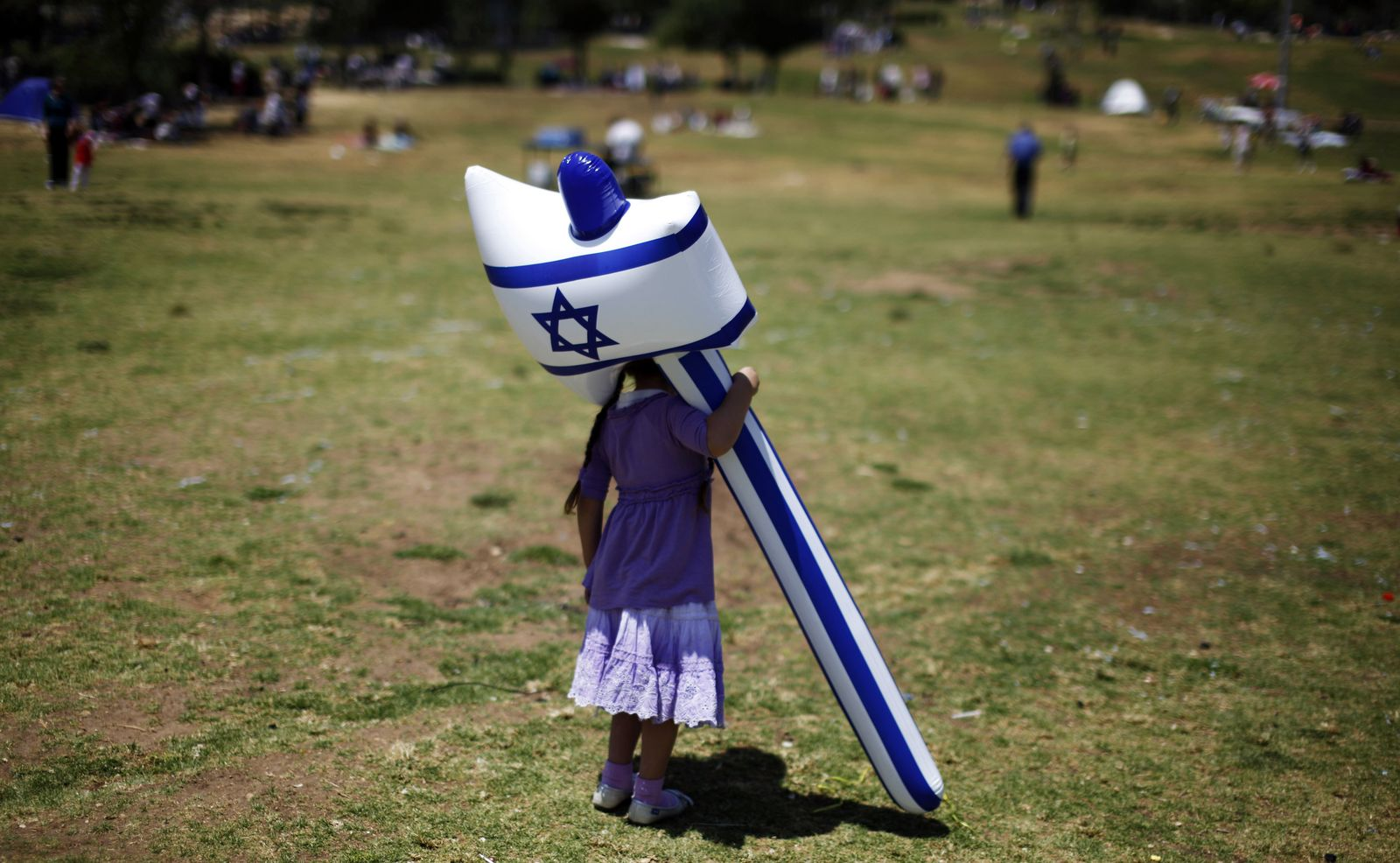 Foto: Una niña israelí juega con un martillo hinchable en un parque de Jerusalén durante el Día de la Independencia, en abril de 2012. (Reuters)