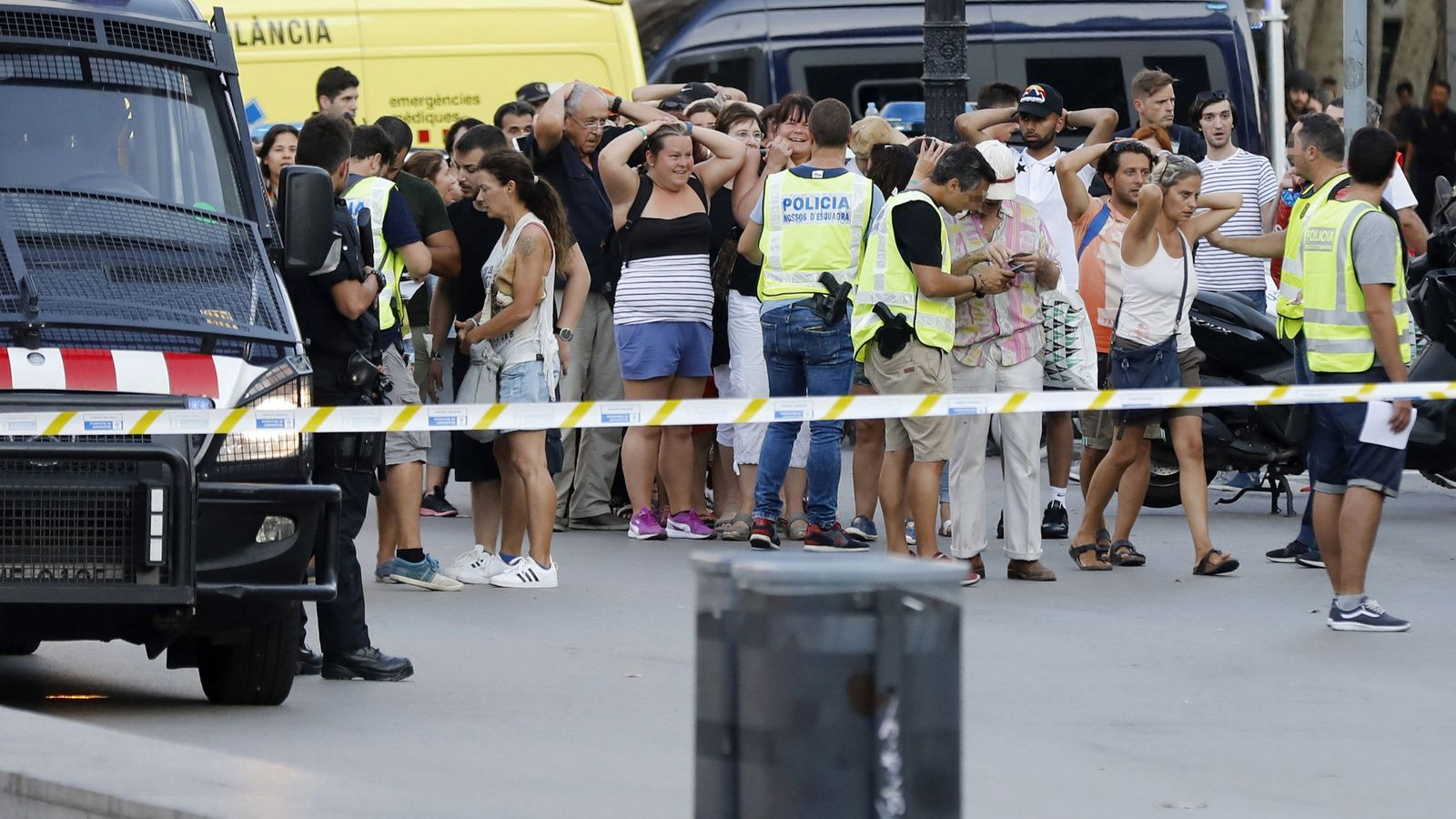 Foto: Un grupo de gente con los brazos en alto ante el despliegue policial en el lugar del atentado. (EFE)