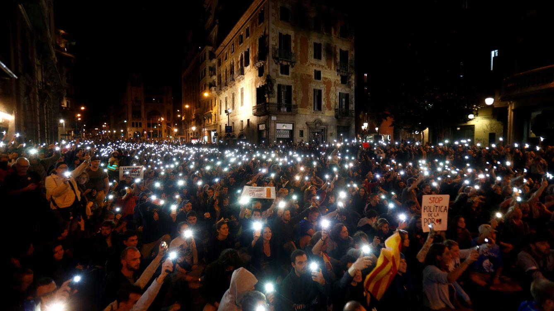 Foto: Los manifestantes catalanes independentistas encienden sus teléfonos frente a la sede de la Policía Nacional. (Reuters)