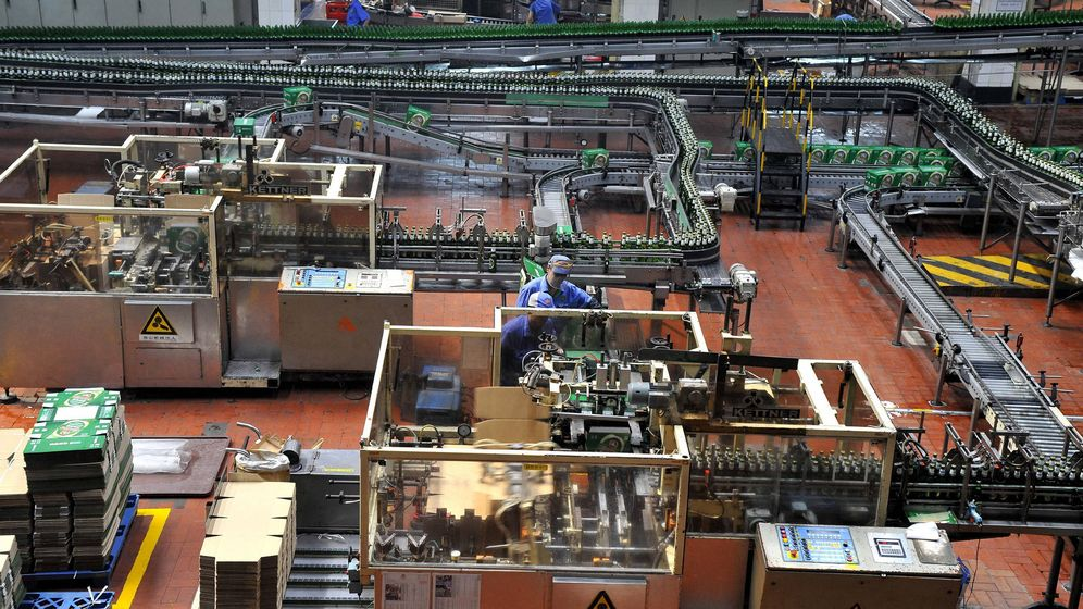 Foto: Dos operarios trabajan en una cadena de montaje de la fábrica de cerveza Tsingtao Brewery Co. (EFE)