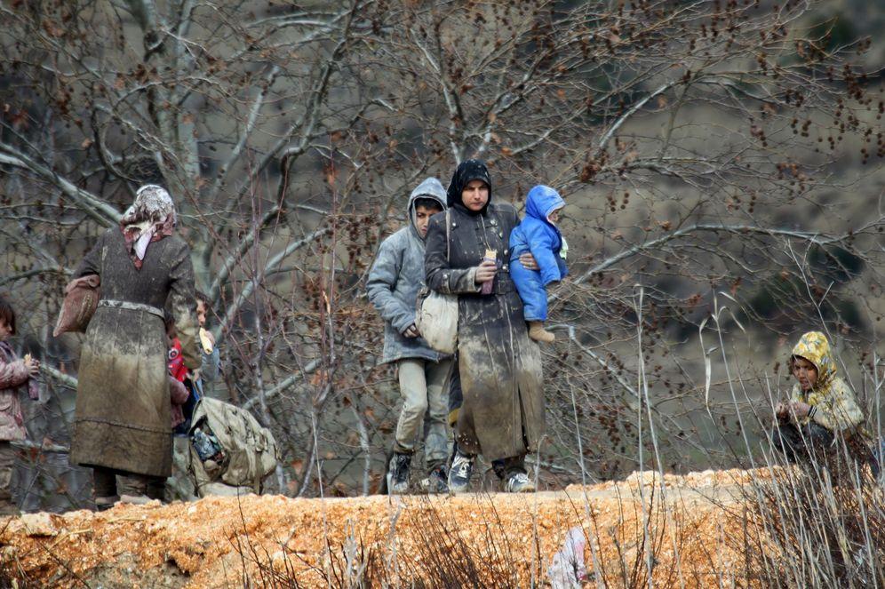 Foto: Sirios que huyen hacia Turquía cubiertos de barro tras cruzar los montes de Latakia en la frontera turca, el 7 de febrero de 2016 (Reuters).