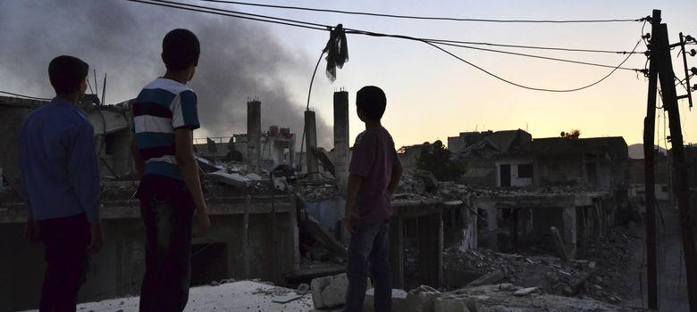 Foto: Un grupo de menores observa una columna de humo tras una explosión en el suburbio de Ghouta, Damasco (Reuters).