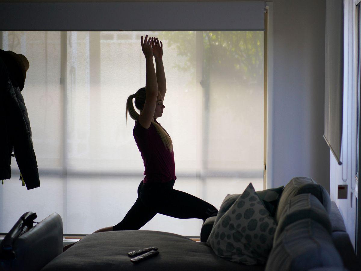 Foto: Una joven practica yoga en su casa. Foto: REUTERS Loren Elliott