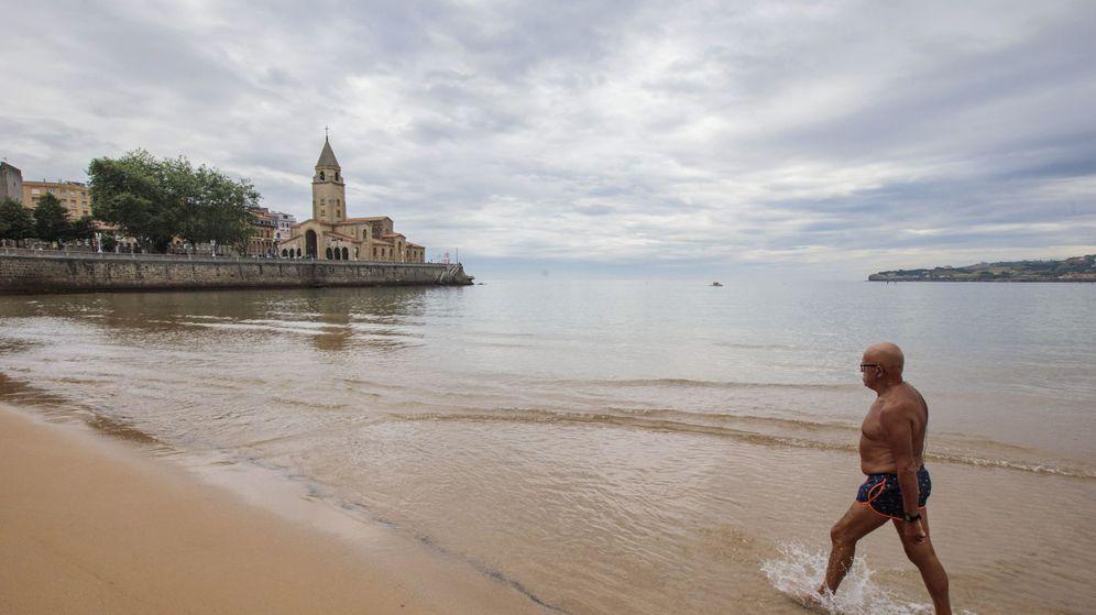 Foto: Un hombre sale del agua en Gijón, ciudad señalada por su nula depuración de residuos. (EFE)