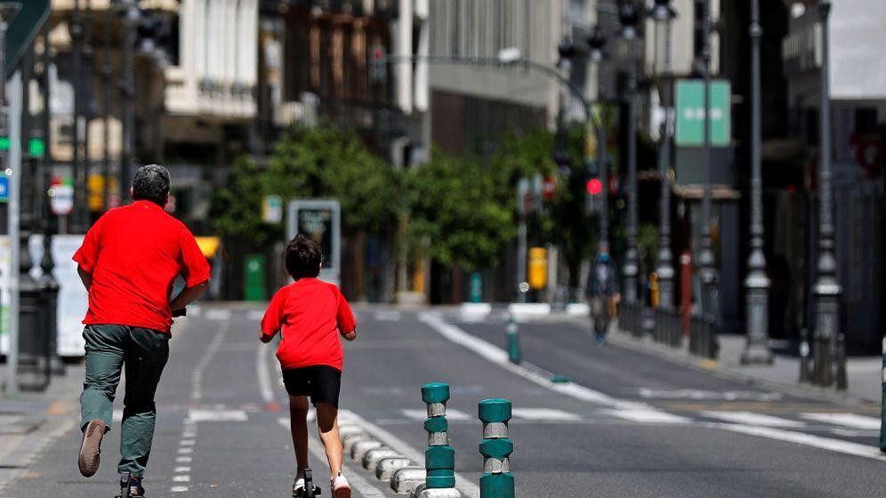 Foto: Un hombre patina con un niño en una calle de Valencia. (EFE)