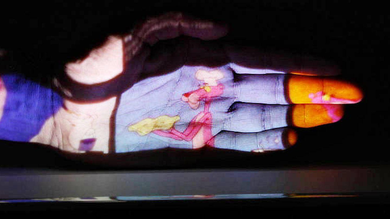 A menos de un palmo de la pared, el proyector muestra una imagen de un par de metros.
