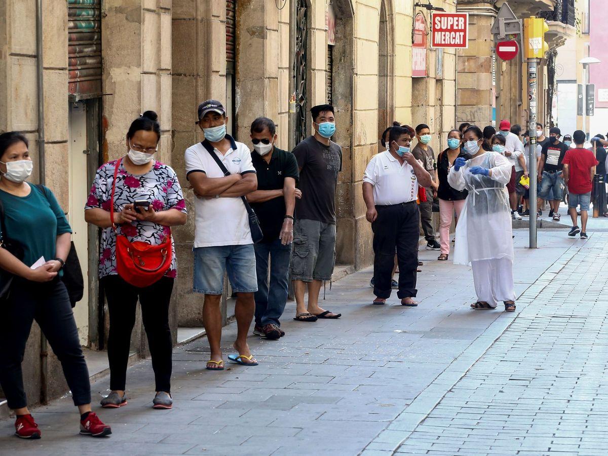 Foto: Varias personas hacen cola para recoger comida este verano en Barcelona (EFE)