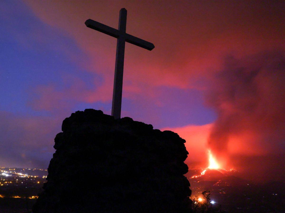 Foto: Un cruz, con la erupción del volcán de fondo. (Reuters)