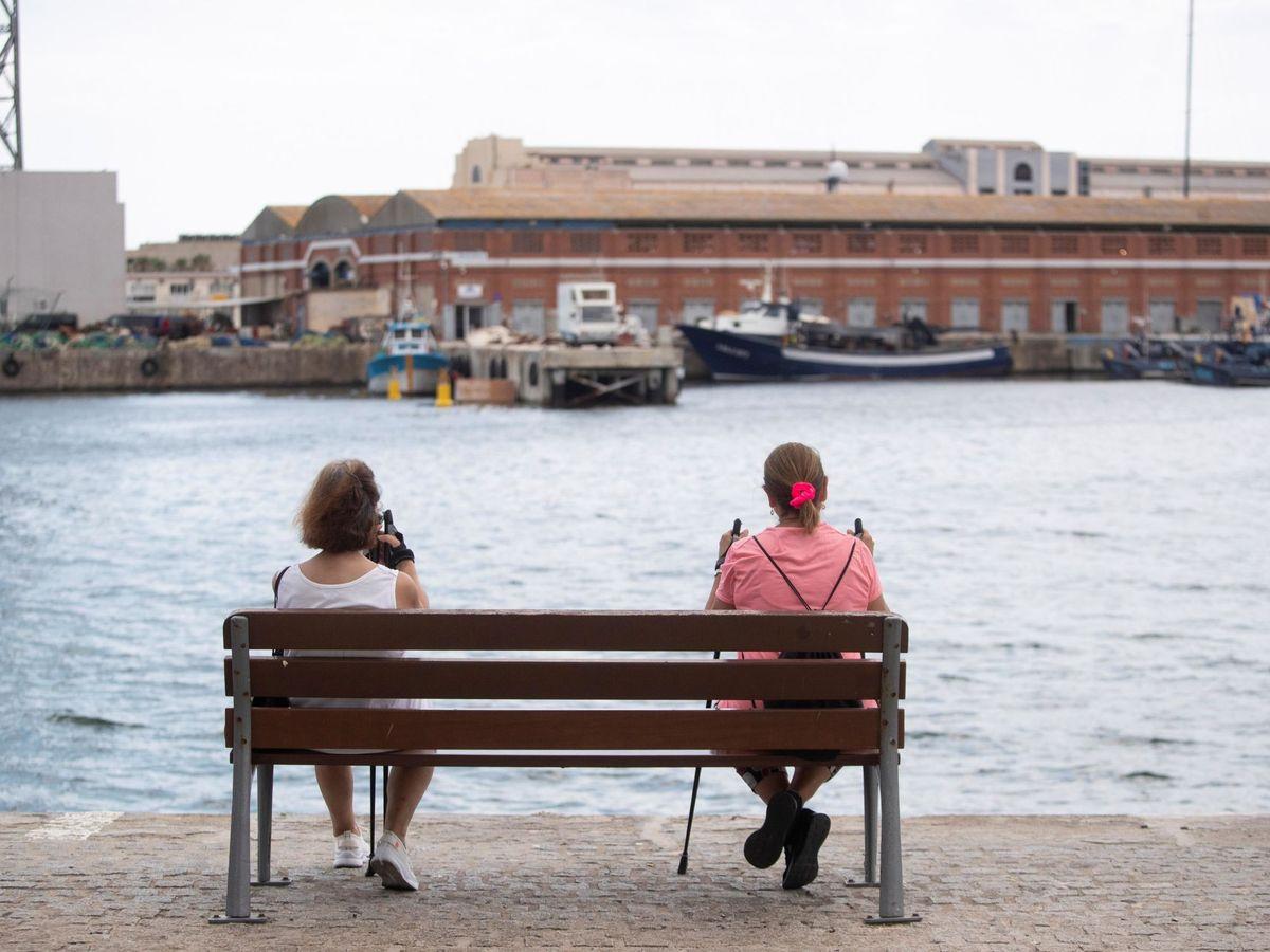Foto: Dos mujeres descansan en un banco en el puerto de Barcelona. (EFE)