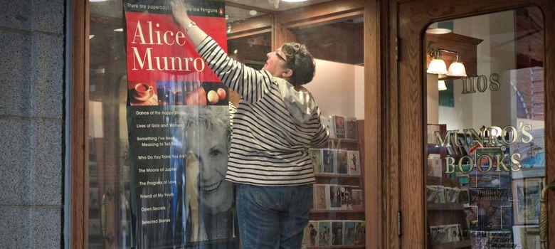 Foto: Una empleada de la Librería Munro, en Victoria (Canadá), coloca un póster de Alice Munro. (Reuters)