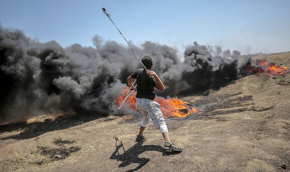 Foto: Un palestino lanza piedras hacia soldados israelíes en una protesta en la frontera de Gaza, el lunes. (EFE)