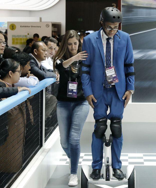 Foto: Una azafata del 'stand' de la multinacional china Xiaomi ayuda a patinar a un visitante en el Mobile World Congress.